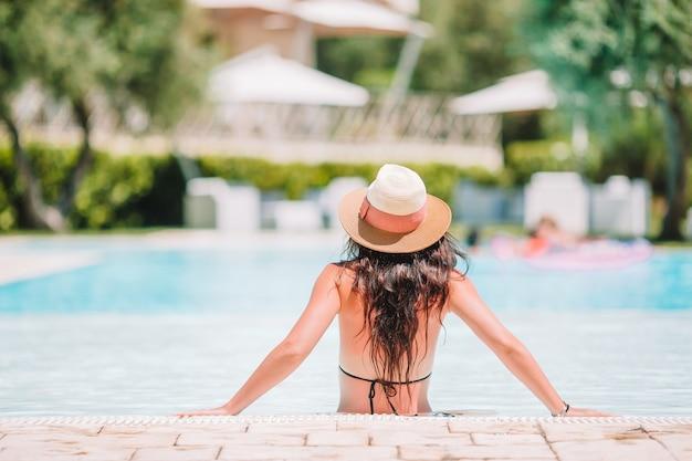 Schöne junge frau, die im swimmingpool sich entspannt.