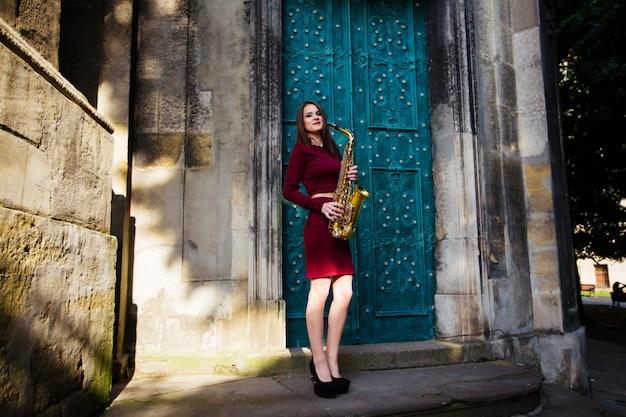Schöne junge frau, die in den stadtstraßen mit ihrem saxophon aufwirft