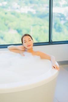 Schöne junge frau, die in der badewanne entspannt