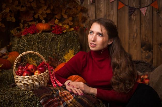 Schöne junge frau, die in der herbsteinstellung auf heu mit einem korb der äpfel und der eberesche sitzt