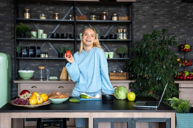 Schöne junge frau, die in der küche aufwirft