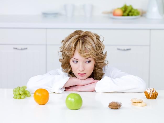 Schöne junge frau, die in der küche sitzt und zwischen gesunden früchten und leckeren kuchen wählt