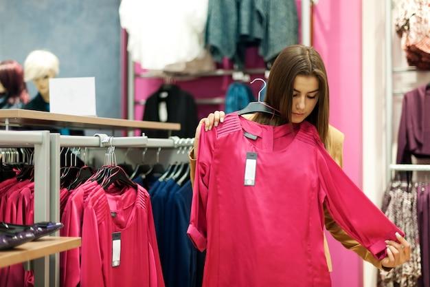 Schöne junge frau, die in einem bekleidungsgeschäft einkauft