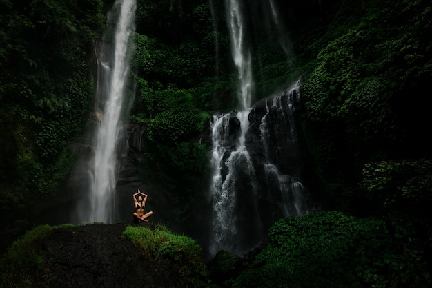 Schöne junge frau, die in lotussitz beim handeln von yoga in einem wunderbaren wald nahe wasserfall meditiert. schönes weibliches übendes yoga auf felsen nahe tropischem wasserfall