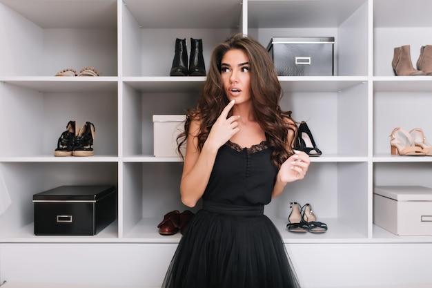 Schöne junge frau, die in luxusgarderobe, ankleidezimmer steht und überlegt, was sie anziehen soll. nachdenklicher blick. trage ein schönes schwarzes kleid.