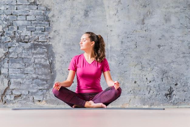 Schöne junge frau, die in meditierender yogaposition sitzt
