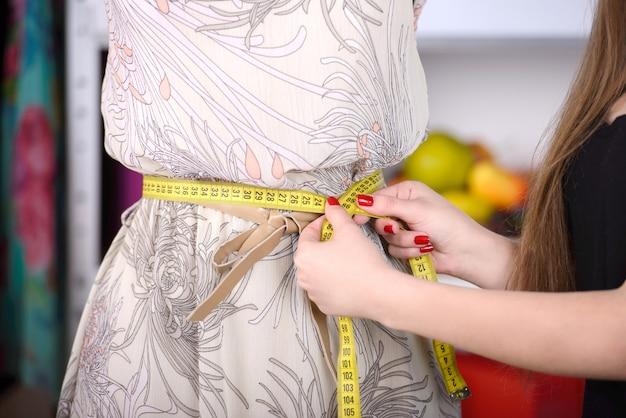 Schöne junge frau, die in mode designstudio arbeitet