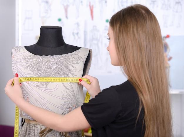 Schöne junge frau, die in mode designstudio arbeitet.