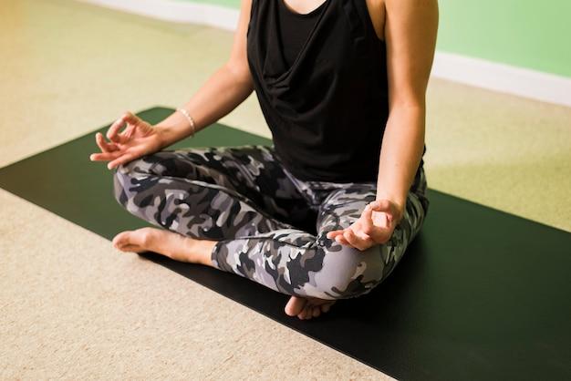 Schöne junge frau, die in yogaposition sitzt und meditiert