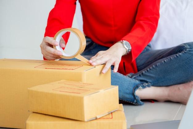 Schöne junge frau, die kästen eines pakets packt. e-commerce und start-up-business-konzept.