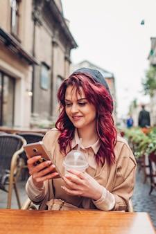Schöne junge frau, die kaffee im café im freien trinkt, während sie smartphone verwendet. porträt eines stilvollen mädchens, das soziales netzwerk überprüft