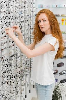 Schöne junge frau, die kamera beim entfernen von brillen von der anzeige im optikspeicher betrachtet