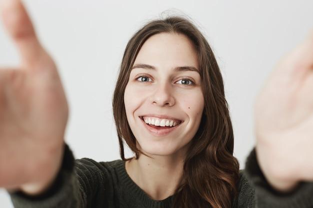 Schöne junge frau, die kamera mit gestreckten händen hält, lächelnd selfie nehmend