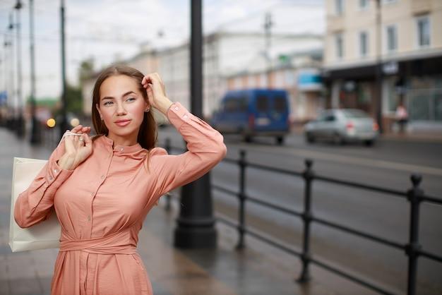 Schöne junge frau, die kleid trägt und auf der stadtstraße aufwirft