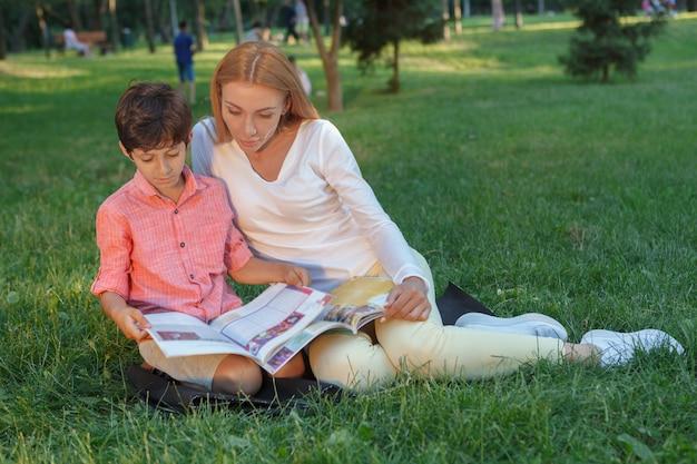 Schöne junge frau, die kleinen jungen unterrichtet und ihm hilft, ein buch zu lesen