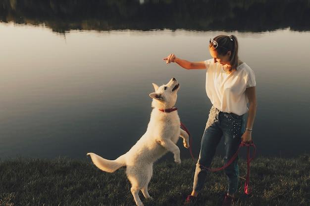 Schöne junge frau, die köder benutzt, um hund neuen trick beizubringen, während er am ufer des ruhigen flusses steht
