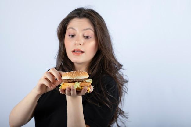 Schöne junge frau, die köstlichen rindfleischburger hält.