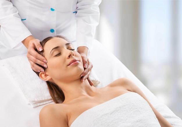 Schöne junge frau, die kopfmassage im wellnesscenter genießt?