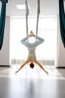 Schöne junge frau, die kopfüber an der hängematte hängt, um pose des antigravitations-yoga zu machen?
