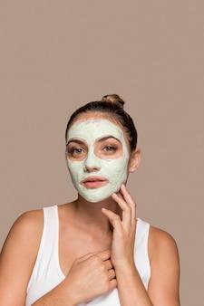 Schöne junge frau, die kosmetische produkte versucht