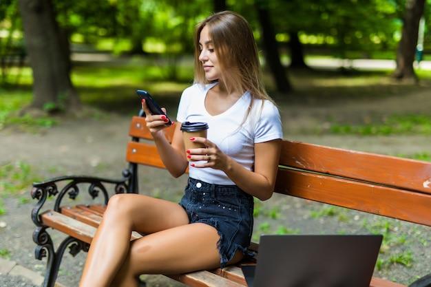 Schöne junge frau, die laptop beim sitzen auf einer bank verwendet, kaffeetasse zum mitnehmen trinkend