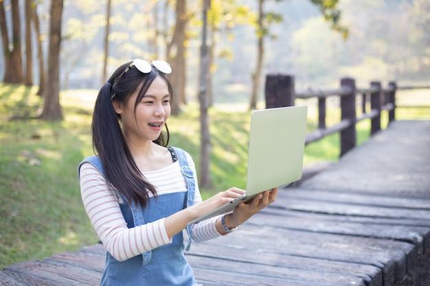Schöne junge frau, die laptop verwendet