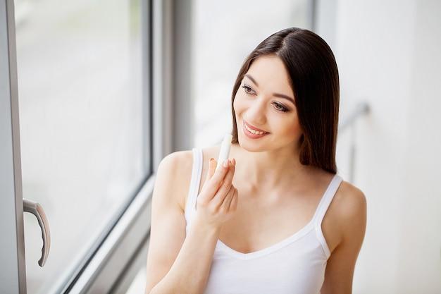Schöne junge frau, die lippenstift anwendet