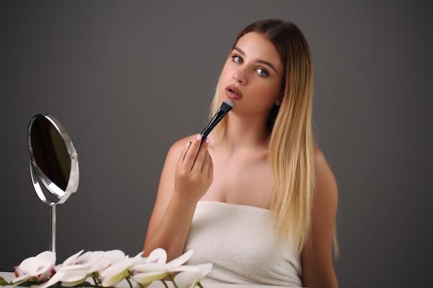 Schöne junge frau, die make-up im badezimmer anwendet.
