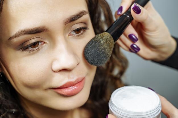 Schöne junge frau, die make-up mit einem pinsel gegen einen grauen hintergrund anwendet