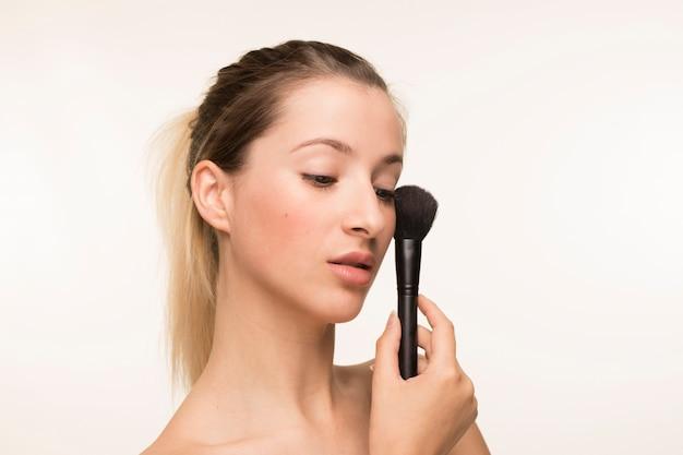 Schöne junge frau, die make-upbürste hält