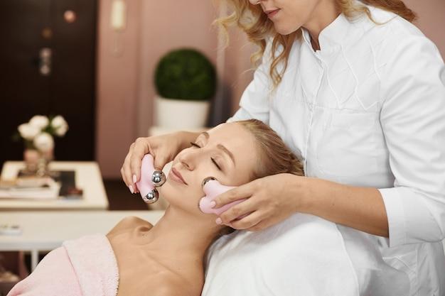 Schöne junge frau, die mikrostromverfahren für das anheben der haut durch kosmetikertherapeutin erhält. gesichtsverjüngung und facelifting mit galvanischer stromtherapie, hautmassage im spa-schönheitssalon