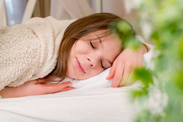 Schöne junge frau, die mit bequemem kissen schläft.