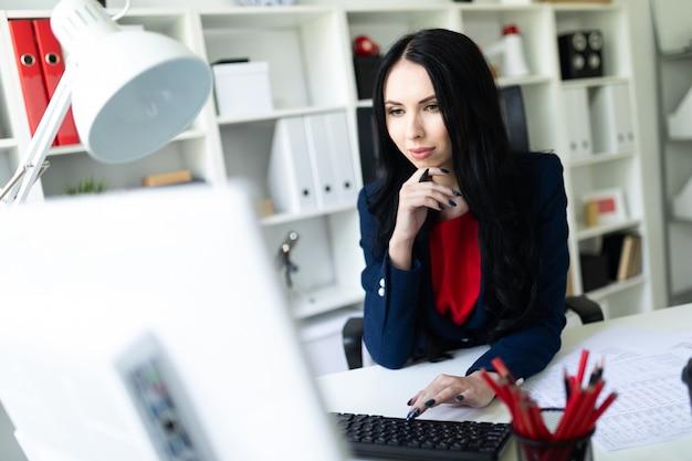 Schöne junge frau, die mit computer und dokumenten im büro am tisch arbeitet.
