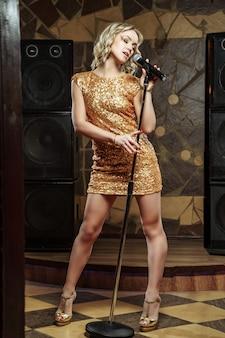 Schöne junge frau, die mit dem mikrofon singt
