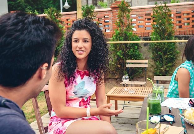 Schöne junge frau, die mit einem freund um den tisch mit gesunden getränken an einem freizeit-sommertag im freien spricht