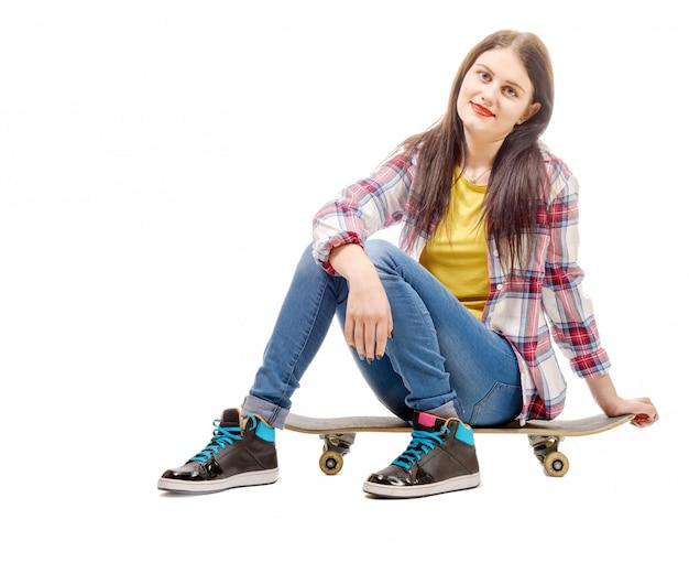 Schöne junge frau, die mit einem skateboard, sitz auf rochen aufwirft