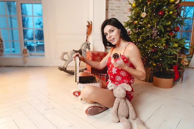Schöne junge frau, die mit einem teddybär durch den weihnachtsbaum spielt