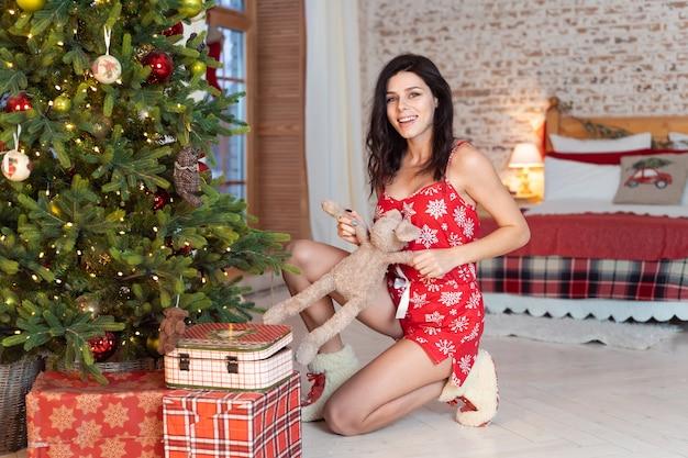 Schöne junge frau, die mit einem teddybären durch den weihnachtsbaum spielt