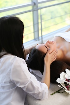 Schöne junge frau, die mit handmassage am beauty spa entspannt
