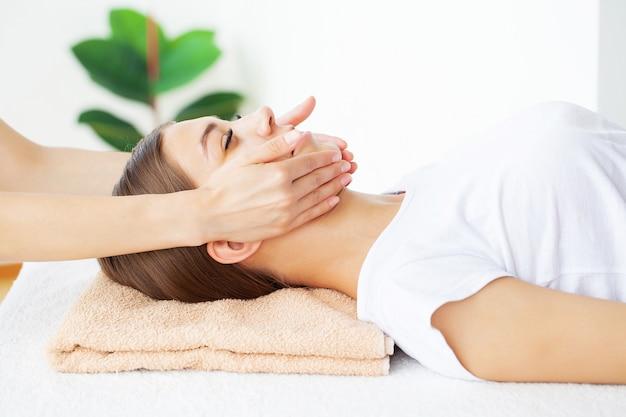 Schöne junge frau, die mit handmassage am schönheits-spa-salon entspannt