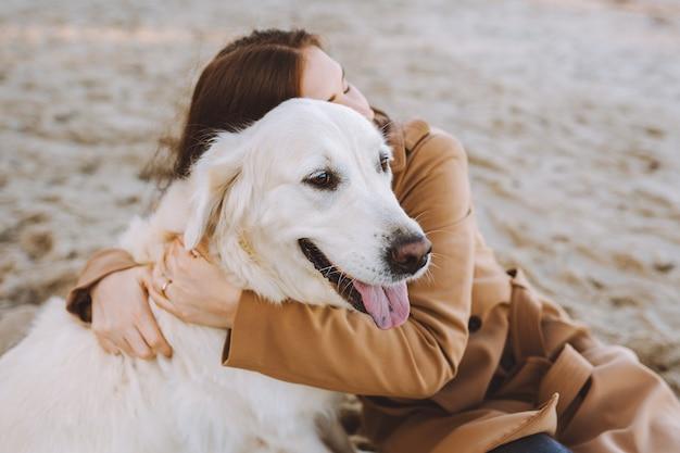 Schöne junge frau, die mit ihrem goldenen retreiver hund am strand am warmen herbsttag umarmt