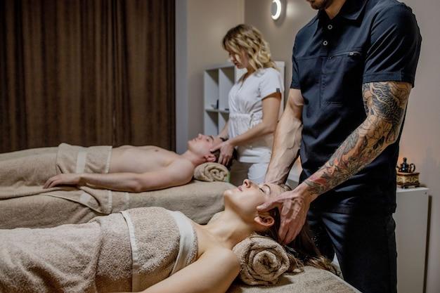 Schöne junge frau, die mit ihrem partner während der traditionellen thai-massage im luxus-spa- und wellnesscenter entspannt.