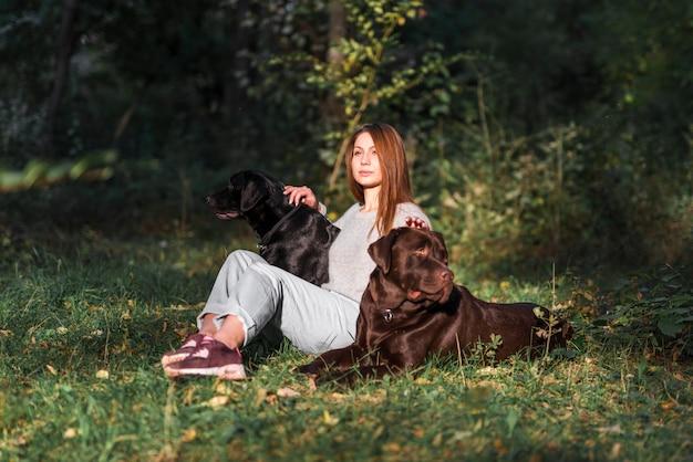 Schöne junge frau, die mit ihren haustieren im park sitzt