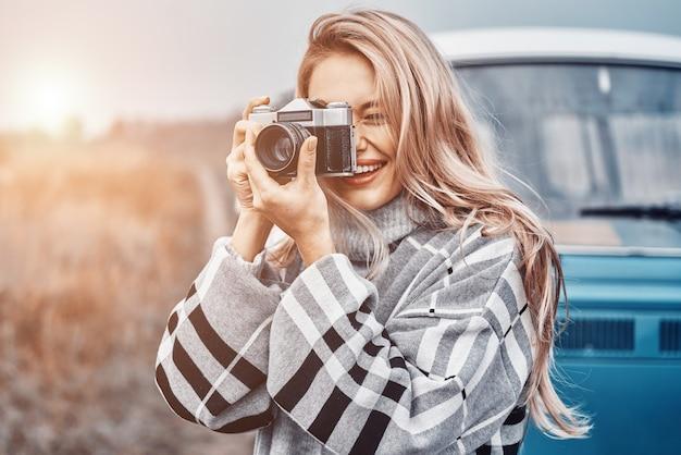 Schöne junge frau, die mit ihrer retro-kamera fotografiert und lächelt, während sie zeit im freien verbringt
