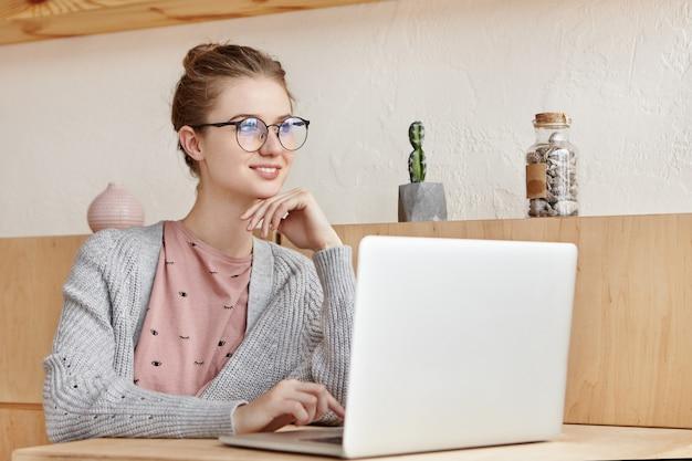 Schöne junge frau, die mit laptop arbeitet