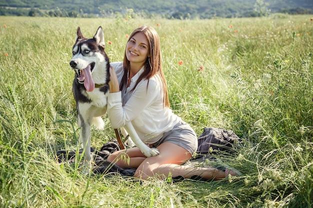Schöne junge frau, die mit lustigem huskyhund draußen im park spielt