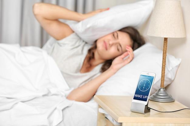 Schöne junge frau, die mit mobilem wecker aufwacht