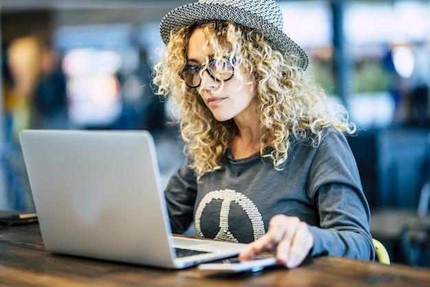 Schöne junge frau, die mit roaming-telefongerät wie digitalem reise-nomaden oder kluger arbeit am bar-café arbeitet