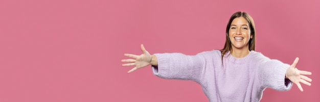 Schöne junge frau, die mit rosa tapete in den rücken aufwirft