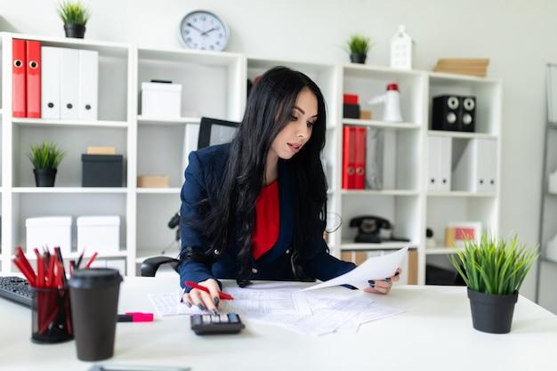 Schöne junge frau, die mit taschenrechner und dokumenten im büro am tisch arbeitet